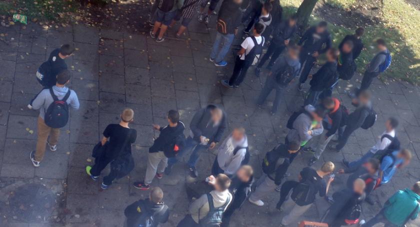 Uczniowie palą papierosy pod jednym z bloków, niedaleko szkoły w Szczecinku