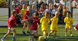 Grali w piłkę na trawie przed ratuszem
