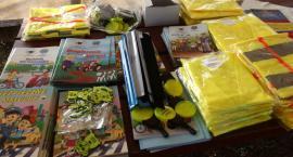 Policjanci wręczają dzieciom edukacyjne książeczki