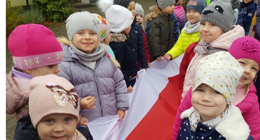 Uroczystości obchody, Przedszkolaki maszerowały metrową flagą Polski - zdjęcie, fotografia
