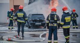 Samochód uderzył w budynek, straż walczy z płomieniami