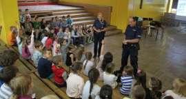 Policjanci rozmawiają z dziećmi o bezpieczeństwie podczas wakacji.