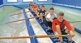 Łodzie w hangarach, zawodnicy na basenie