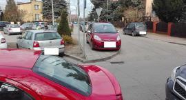 Samochody na chodnikach i trawnikach. Piesi chodzą ulicą