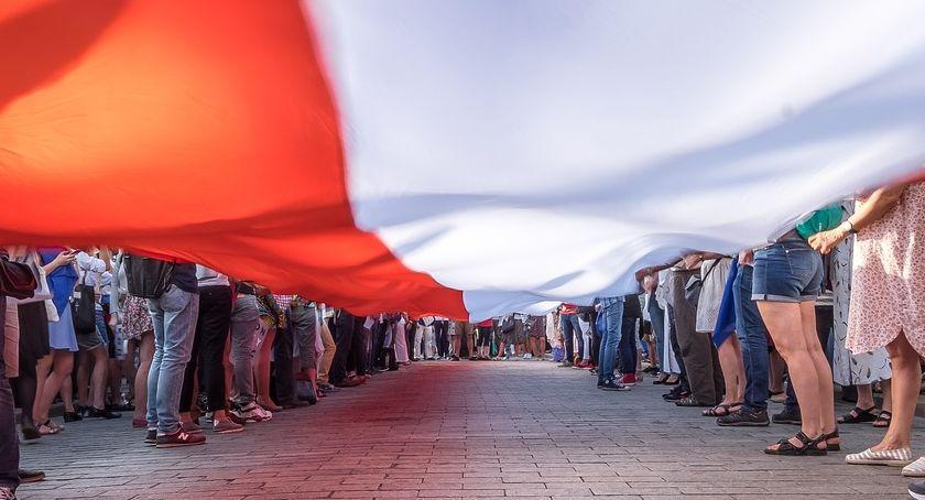 Ludzie trzymający rozciągniętą flagę Polski