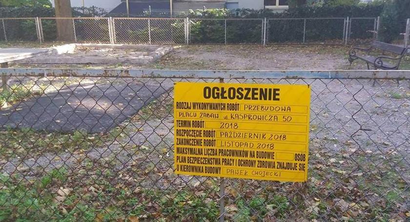 Na głównym zdjęciu znajduje się tablica informacyjna. To ogłoszenie, które pokazuje wiadomość na temat tego, kto przebuduje plac zabaw. W tle stoi budynek, na pierwszym planie ogrodzenie.