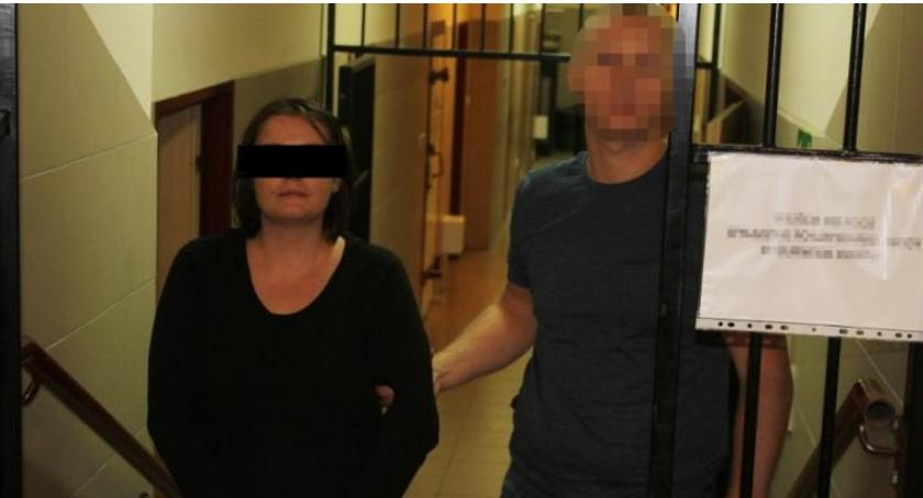 Na pierwszym planie znajduje się kobieta, jedna ze sprawców zabójstwa. Pilnuje jej policjant, prowadząc do pomieszczenia w areszcie. Stoją na korytarzu.