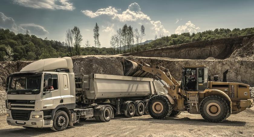 Ciężarówka i koparka stojące na pustkowiu.