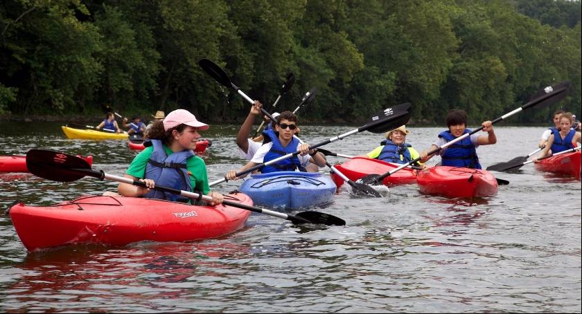 Zdjęcie przedstawia kajakarzy, którzy podróżują z nurtem rzeki. Na podobną aktywność zapraszamy już za miesiąc.