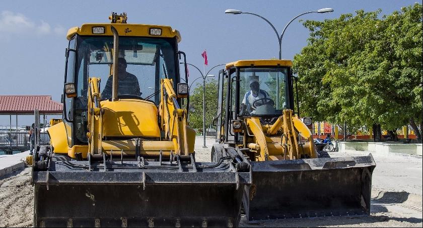 Zdjęcie przedstawia koparki, które zajmują się robotami drogowymi. Między innymi taki ciężki sprzęt będzie wykorzystywany podczas remontów drogowych w Skierniewicach.